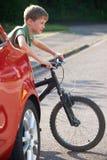 Bici del montar a caballo del niño de detrás el coche parqueado Imagen de archivo