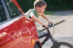 Bici del montar a caballo del niño de detrás el coche parqueado Foto de archivo libre de regalías