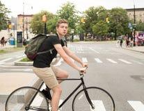 Bici del montar a caballo del estudiante universitario que cruza el paso de peatones en la ciudad Foto de archivo libre de regalías