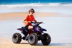 Bici del patio del montar a caballo del adolescente en la playa Foto de archivo