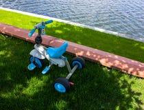 Bici del triple del ` s de los niños en la hierba en el jardín Imágenes de archivo libres de regalías
