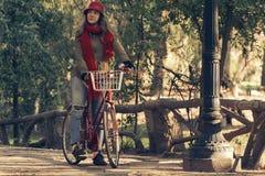 Bici del vintage del montar a caballo de la muchacha el temporada de otoño en el parque Imágenes de archivo libres de regalías