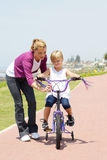 Bici della figlia della madre Fotografia Stock