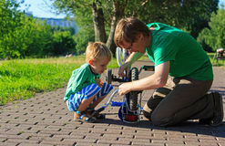 Bici della riparazione del figlio e del padre Fotografia Stock Libera da Diritti