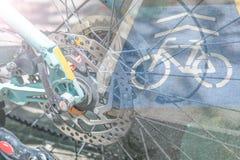 Bici della ruota di doppia esposizione con il segno della bici sul percorso della bici Immagini Stock Libere da Diritti