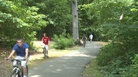 Bici di camminata e di guida della gente in parco (1 di 3) archivi video