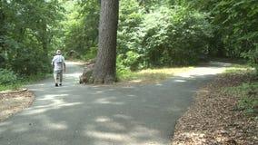 Bici di camminata e di guida della gente in parco (3 di 3) archivi video