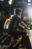 Bici di esercizio asiatiche dell'uomo alla palestra Fotografie Stock