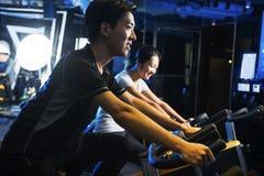 Bici di esercizio asiatiche dell'uomo alla palestra Fotografia Stock Libera da Diritti