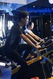 Bici di esercizio asiatiche dell'uomo alla palestra Immagini Stock