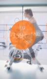 Bici di esercizio di guida della donna con l'interfaccia futuristica accanto lei Immagini Stock Libere da Diritti