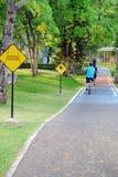 Bici di giro della gente in pista ciclabile in parco pubblico Immagine Stock