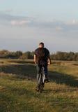 Bici di guida del ciclista del giovane in legno al tramonto Fotografia Stock