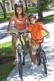 Bici di guida del figlio del ragazzo della madre della donna dell'afroamericano Fotografia Stock