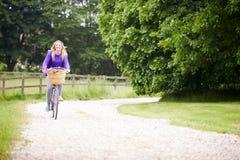 Bici di guida dell'adolescente lungo il vicolo del paese Immagini Stock