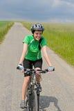 Bici di guida della donna sul prato della pista ciclabile Immagine Stock