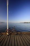 Bici en el muelle cerca del agua Fotos de archivo libres de regalías