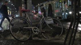 Bici en la calle de la ciudad del invierno de la noche Gente y tráfico del transporte en fondo metrajes
