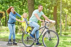 Bici felice di guida della famiglia al parco fotografia stock libera da diritti