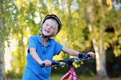 Bici feliz del montar a caballo del adolescente en el parque Fotografía de archivo