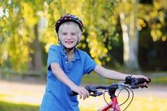 Bici feliz del montar a caballo del adolescente en el parque Imagen de archivo