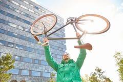 Bici fija de levantamiento del engranaje del hombre joven del inconformista en ciudad Fotografía de archivo