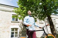 Bici fija del engranaje del hombre joven feliz del inconformista que monta Imagen de archivo