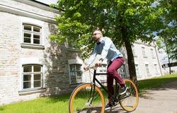 Bici fija del engranaje del hombre joven feliz del inconformista que monta Imágenes de archivo libres de regalías