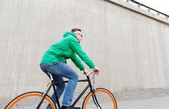 Bici fija del engranaje del hombre joven feliz del inconformista que monta Fotos de archivo libres de regalías