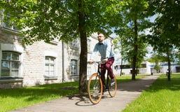 Bici fija del engranaje del hombre joven feliz del inconformista que monta Fotografía de archivo