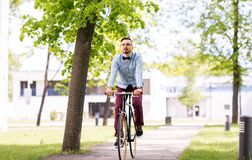 Bici fija del engranaje del hombre joven feliz del inconformista que monta fotografía de archivo libre de regalías