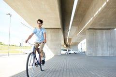 Bici fissa di guida dell'ingranaggio del giovane uomo dei pantaloni a vita bassa Fotografia Stock Libera da Diritti