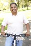 Bici hispánica mayor del montar a caballo del hombre en parque Fotos de archivo