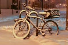 Bici innevata su una sera di inverno in Ann Arbor del centro, Michigan fotografia stock