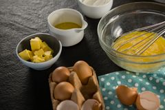 Bici jajka, jajeczna taca, masło, olej i mąka utrzymujący na czarnej powierzchni, zdjęcie stock