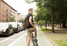 Bici joven del montar a caballo del inconformista que mira detrás en la ciudad Imagenes de archivo