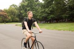 Bici joven moderna del paseo del estudiante universitario en el parque Fotografía de archivo