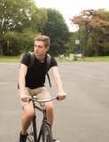 Bici joven moderna del paseo del estudiante universitario en el parque Fotografía de archivo libre de regalías