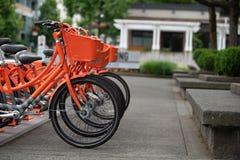 Bici locative arancio sulla via fotografia stock