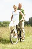 Bici madura del montar a caballo de los pares en campo Foto de archivo