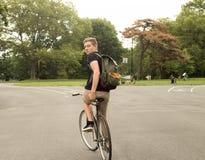 Bici moderna del ridinge del estudiante universitario en el parque que mira detrás Fotografía de archivo libre de regalías