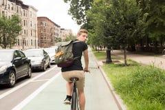 Bici moderna joven del montar a caballo del hombre del inconformista que mira detrás en la ciudad Imagenes de archivo
