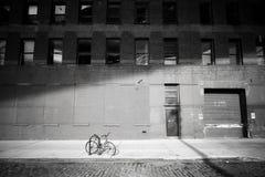Bici olvidada Monte en bicicleta bloqueado por una calle en la vecindad de Dumbo Foto de archivo libre de regalías