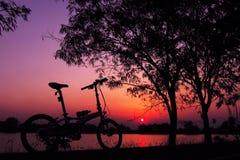 Bici plegable en la silueta de la puesta del sol Imagen de archivo libre de regalías