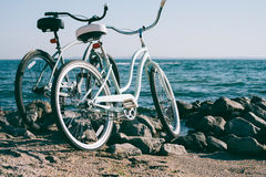Bici retra dos en la playa contra el mar azul imagenes de archivo
