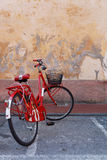 Bici roja en una pared roja Imágenes de archivo libres de regalías