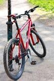 Bici roja que se coloca cerca del pilar Fotos de archivo libres de regalías