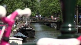 Bici rosada y blanca al canal de Bloemgracht en Amsterdam almacen de metraje de vídeo