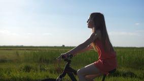 Bici teenager sveglia di guida della ragazza in campagna stock footage