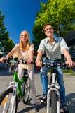 Bici urbana di guida delle coppie nel tempo libero in città Fotografie Stock